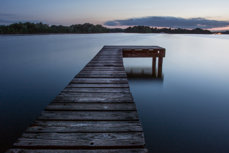Dock on calm water at dusk